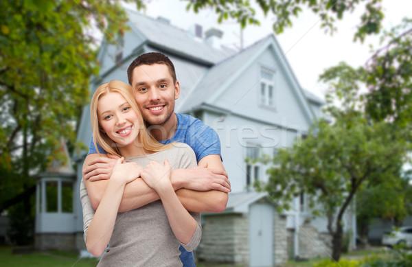 smiling couple hugging over house background Stock photo © dolgachov