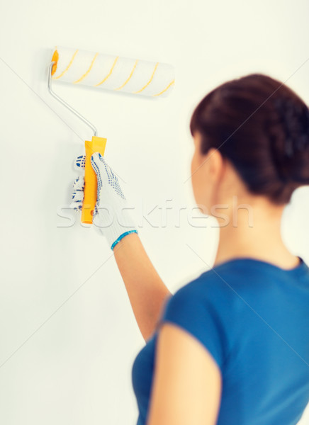 Stock photo: woman with roller and paint colouring the wall