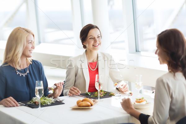 Feliz mulheres alimentação falante restaurante pessoas Foto stock © dolgachov