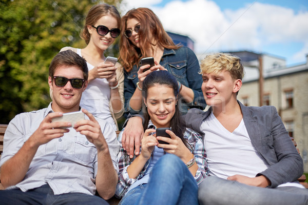 students or teenagers with smartphones at campus Stock photo © dolgachov