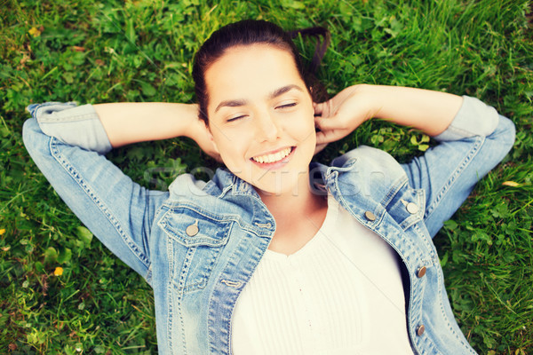 smiling young girl with closed eyes lying on grass Stock photo © dolgachov