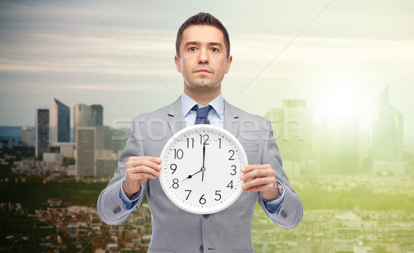 businessman in suit holding clock with 8 o'clock Stock photo © dolgachov