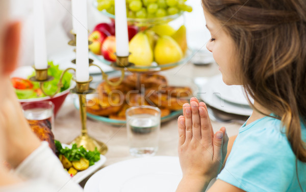 Stock photo: close up of girl praying at holiday dinner
