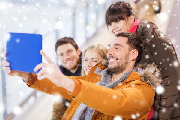 Stock photo: happy friends with tablet pc on skating rink