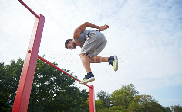 young man jumping on horizontal bar outdoors Stock photo © dolgachov