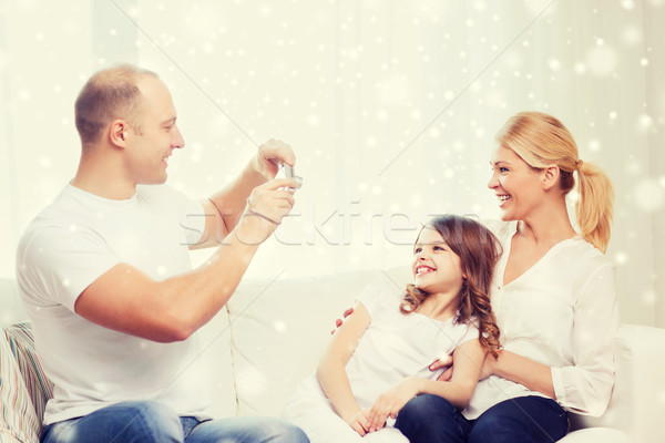 happy family with camera taking picture at home Stock photo © dolgachov