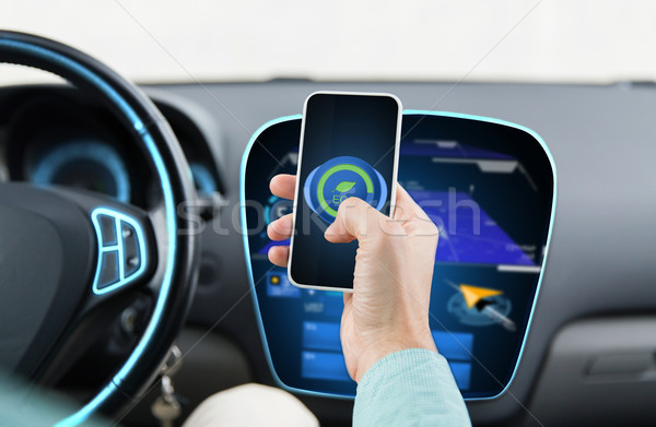 man driving car and setting eco mode on smartphone Stock photo © dolgachov