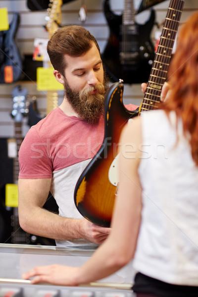 Assistant client guitare musique magasin Photo stock © dolgachov