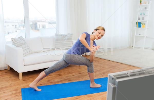 woman making yoga low angle lunge pose on mat Stock photo © dolgachov