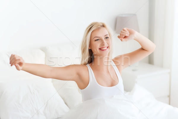 young woman stretching in bed after waking up Stock photo © dolgachov