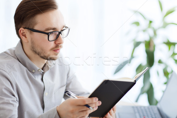 creative male worker with book at home office Stock photo © dolgachov