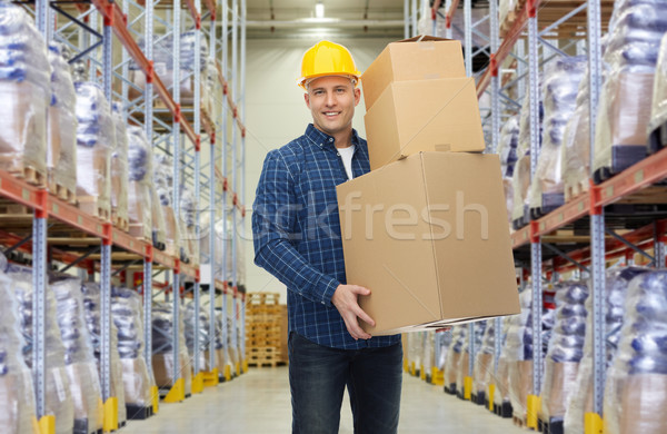 happy man or loader with box at warehouse Stock photo © dolgachov