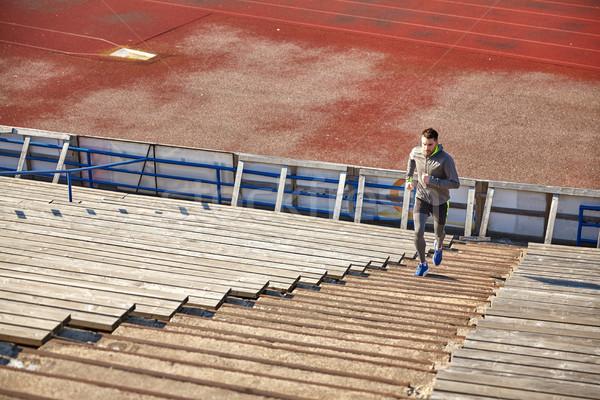 Gelukkig jonge man lopen naar boven stadion fitness Stockfoto © dolgachov