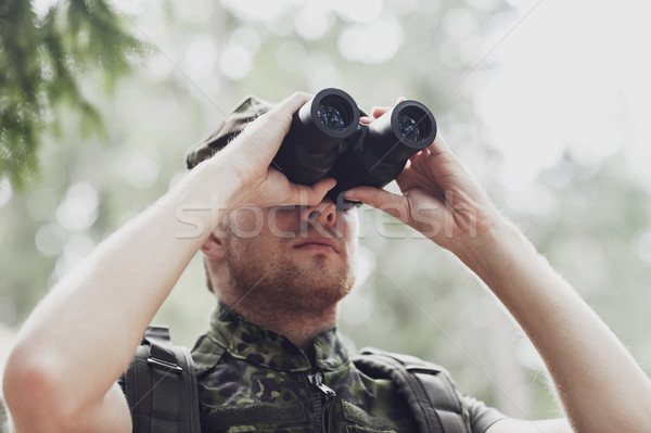 young soldier or hunter with binocular in forest Stock photo © dolgachov
