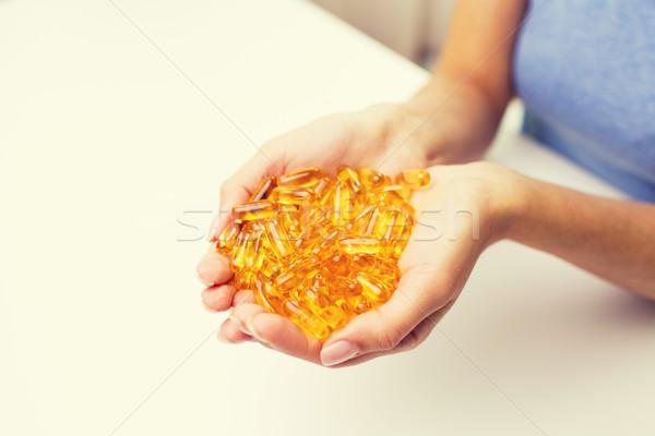 Közelkép nő kezek tart tabletták kapszulák Stock fotó © dolgachov