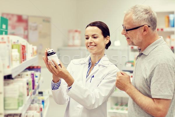 pharmacist showing drug to senior man at pharmacy Stock photo © dolgachov