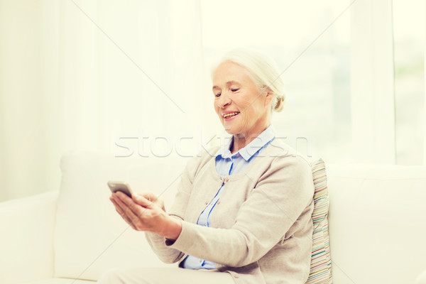 senior woman with smartphone texting at home Stock photo © dolgachov