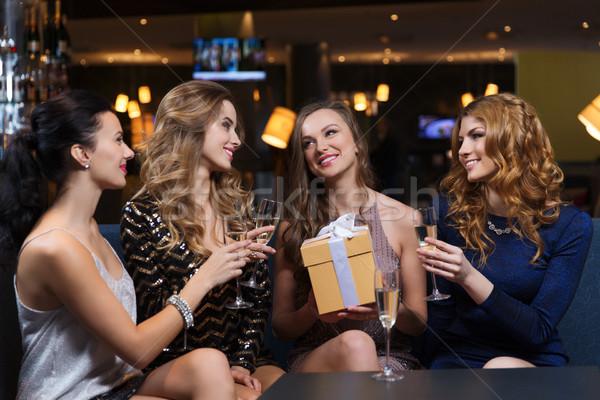 Felice donne champagne regalo night club celebrazione Foto d'archivio © dolgachov