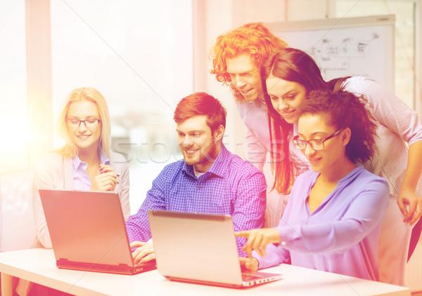 Sorridente equipe laptop informática escritório negócio Foto stock © dolgachov