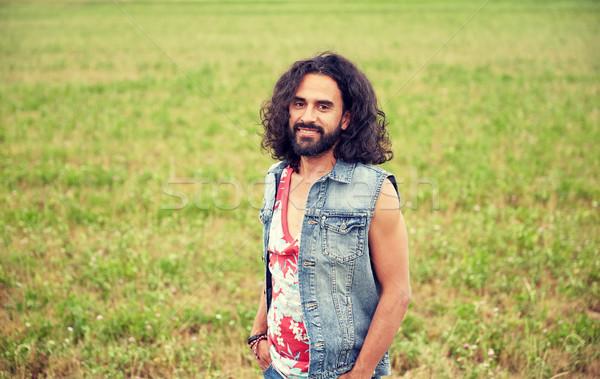 Glimlachend jonge hippie man groene veld Stockfoto © dolgachov