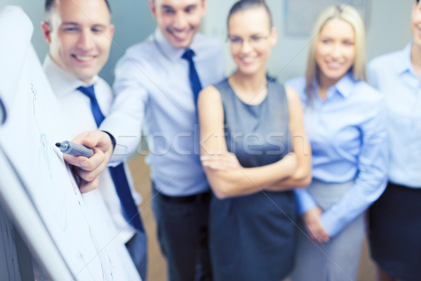 smiling business team with charts on flip board Stock photo © dolgachov