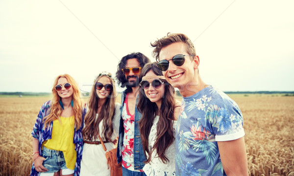 smiling young hippie friends on cereal field Stock photo © dolgachov
