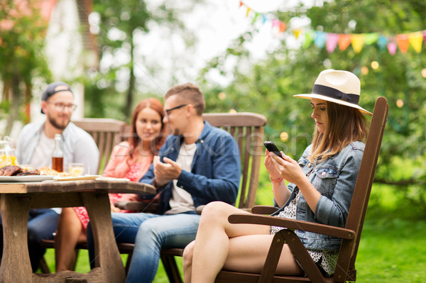 woman with smartphone and friends at summer party Stock photo © dolgachov