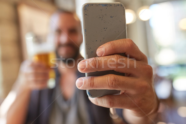 close up of man with smartphone and beer at pub Stock photo © dolgachov