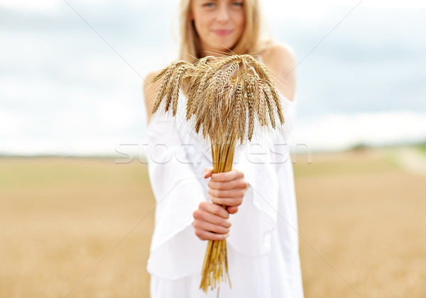 Stock photo: close up of happy woman with cereal spikelets