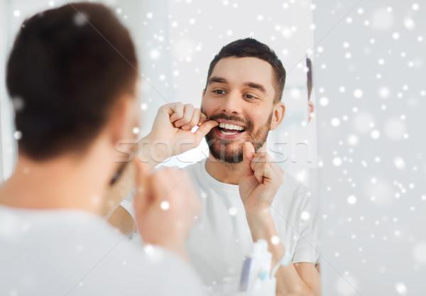 man with dental floss cleaning teeth at bathroom Stock photo © dolgachov