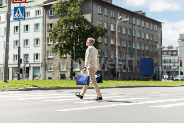 Idős férfi bevásárlótáskák sétál zebra vásár Stock fotó © dolgachov