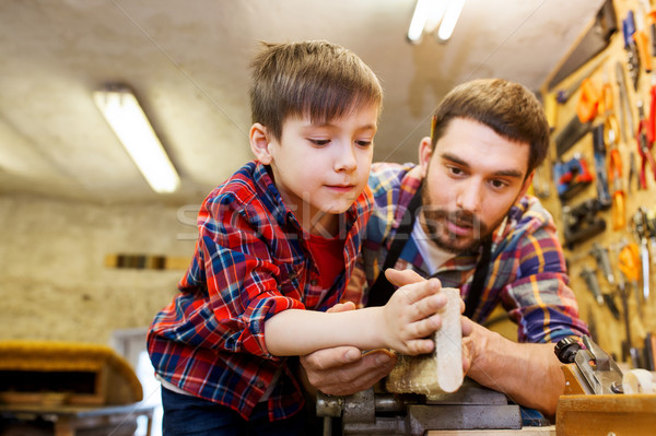 father and little son with wood plank at workshop Stock photo © dolgachov