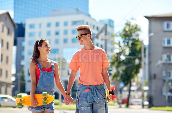 teenage couple with skateboards on city street Stock photo © dolgachov