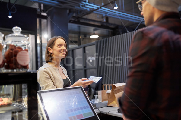 happy woman paying money to seller at cafe Stock photo © dolgachov