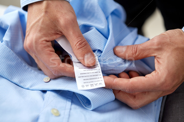 hands with shirt and care instruction label Stock photo © dolgachov