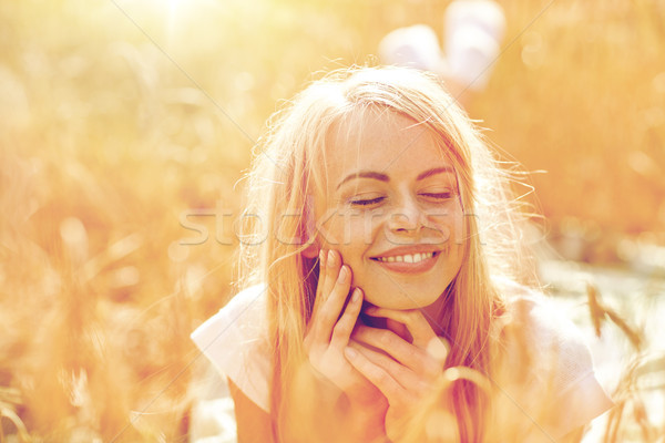 happy woman or teen girl lying in cereal field Stock photo © dolgachov