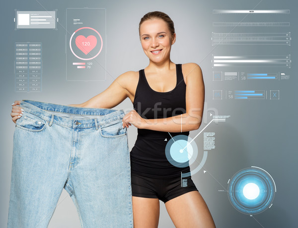 young slim sporty woman showing large size pants Stock photo © dolgachov
