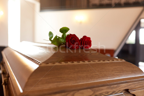 red rose flowers on wooden coffin in church Stock photo © dolgachov