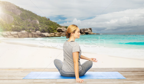 woman doing yoga in twist pose on beach Stock photo © dolgachov