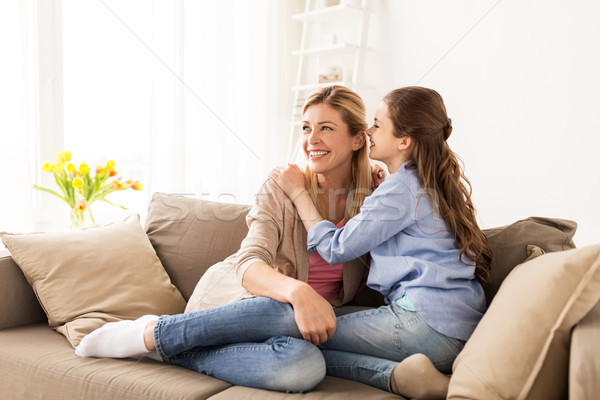 happy girl whispering secret to her mother at home Stock photo © dolgachov