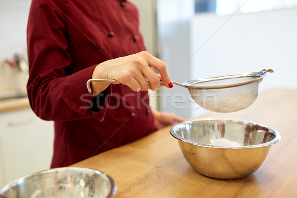 chef with flour in bowl making batter or dough Stock photo © dolgachov