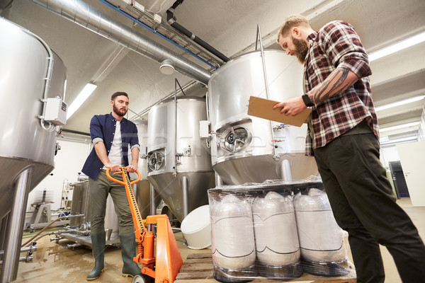 men with beer kegs and clipboard at craft brewery Stock photo © dolgachov