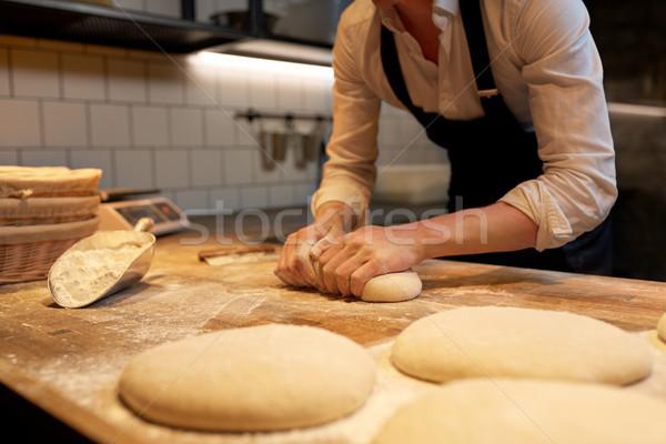 baker making bread dough at bakery kitchen Stock photo © dolgachov
