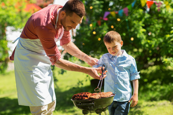 father and son cooking meat on barbecue grill Stock photo © dolgachov