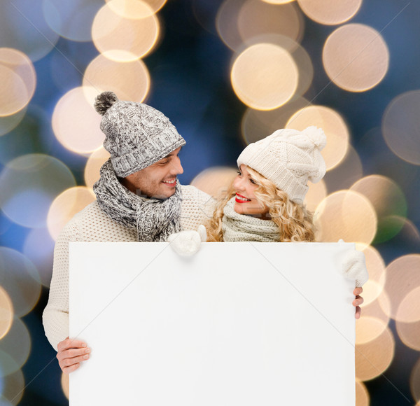 couple in winter clothes with blank white board Stock photo © dolgachov