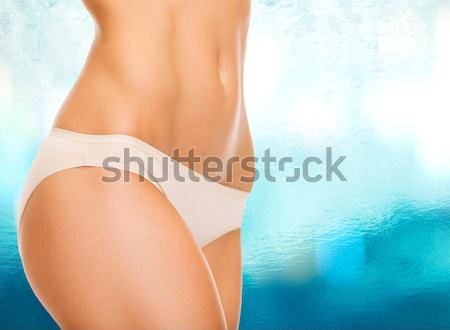 woman pointing at her abs Stock photo © dolgachov