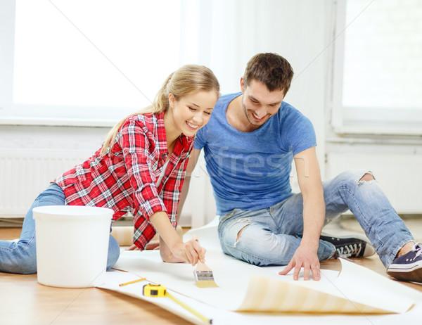 smiling couple smearing wallpaper with glue Stock photo © dolgachov