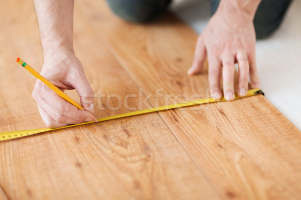 Stock photo: close up of male hands measuring wood flooring