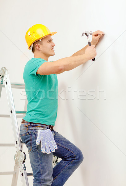 smiling man in helmet hammering nail in wall Stock photo © dolgachov
