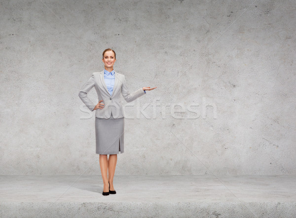 businesswoman showing something on her hand Stock photo © dolgachov